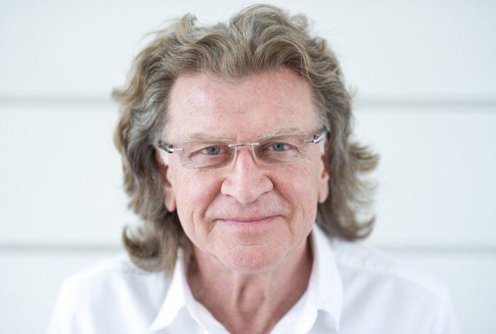 Mężczyzna w dłuższych włosach i białej koszuli