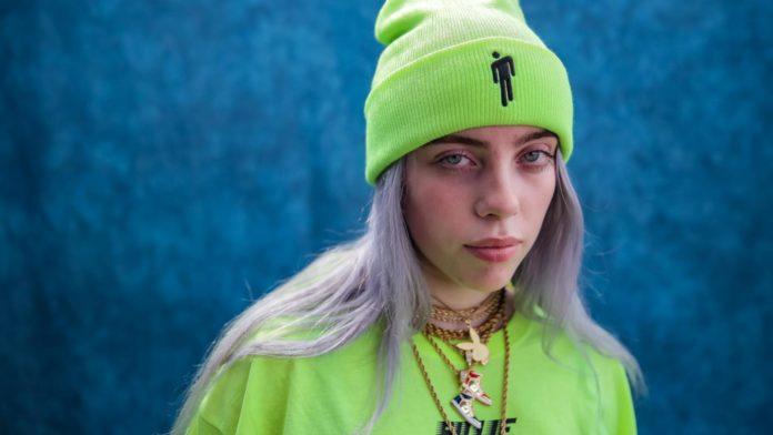 Zdjęcie przedstawia młodą artystkę BBillie Eilish, w jaskrawo zielonej czapce i bluzce w tym samym kolorze. Na szyi ma wiele, złotych wisiorów