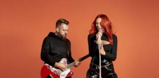 Kobieta przy mikrofonie i mężcyzna z gitarą na pomarańczowym tle