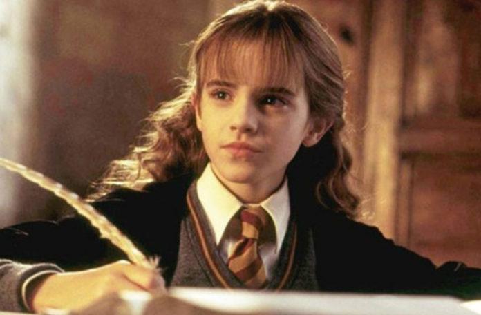 Dziewczyna siedząca przy biurku z piórem
