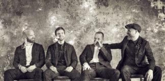 Czarno-białe zdjęcie przedstawiające czwórkę ludzi na krzesłach