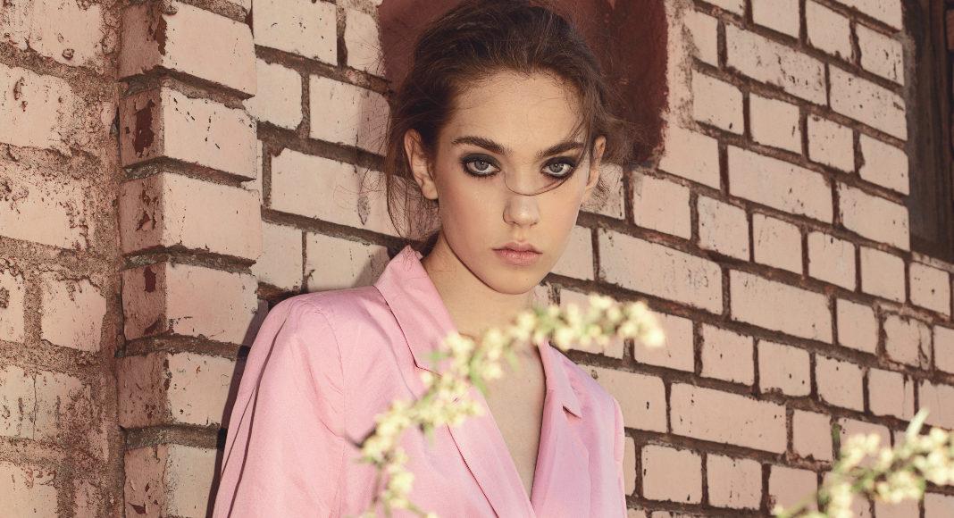 Dziewczyna w różowej marynarce na tle muru