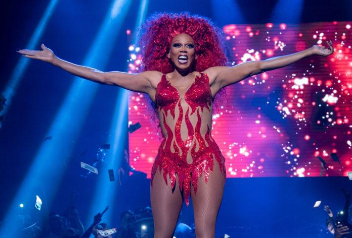 Drag queen w rudej peruce i czerwonej skąpej sukience