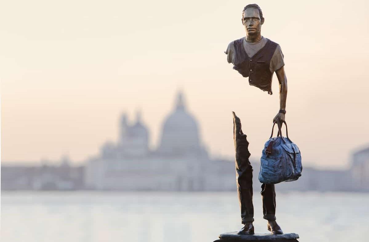 Zdjęcie przedstawia rzeźbę z brązu ukazującą podróżnego, z pustką w centrum jego postaci