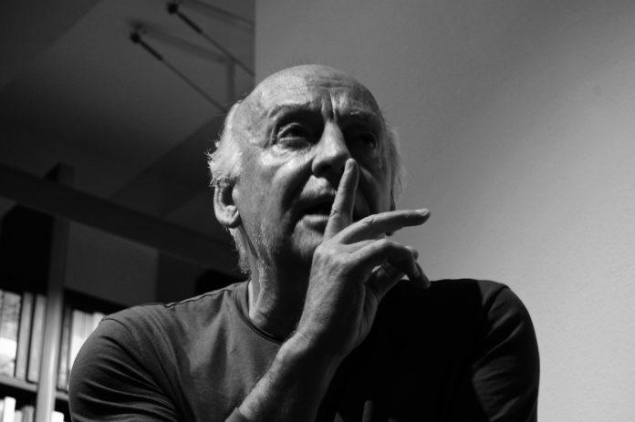 Starszy mężczyzna trzymający palec przy ustach
