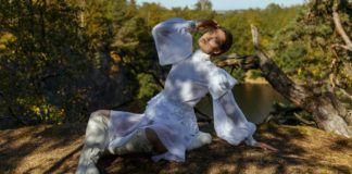 Dziewczyna w białej sukience siedząca na skarpie