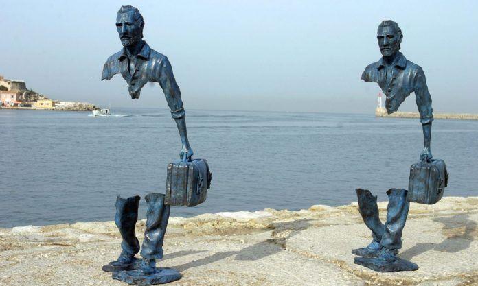 Zdjęcie przedstawia rzeźbę z brązu ukazującą dwoje podróżnych, z pustką w centrum jego postaci