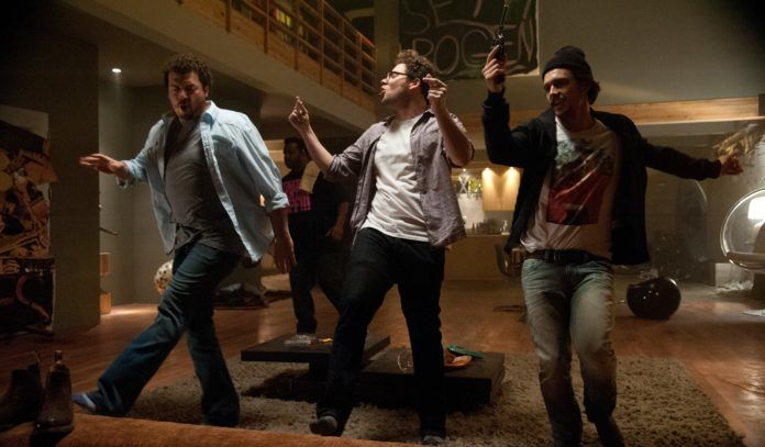 Trzech tańczących mężczyzn. Jeden z nich trzyma pistolet