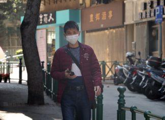 Mężczyzna w masce idący chodnikiem z telefonem w ręku