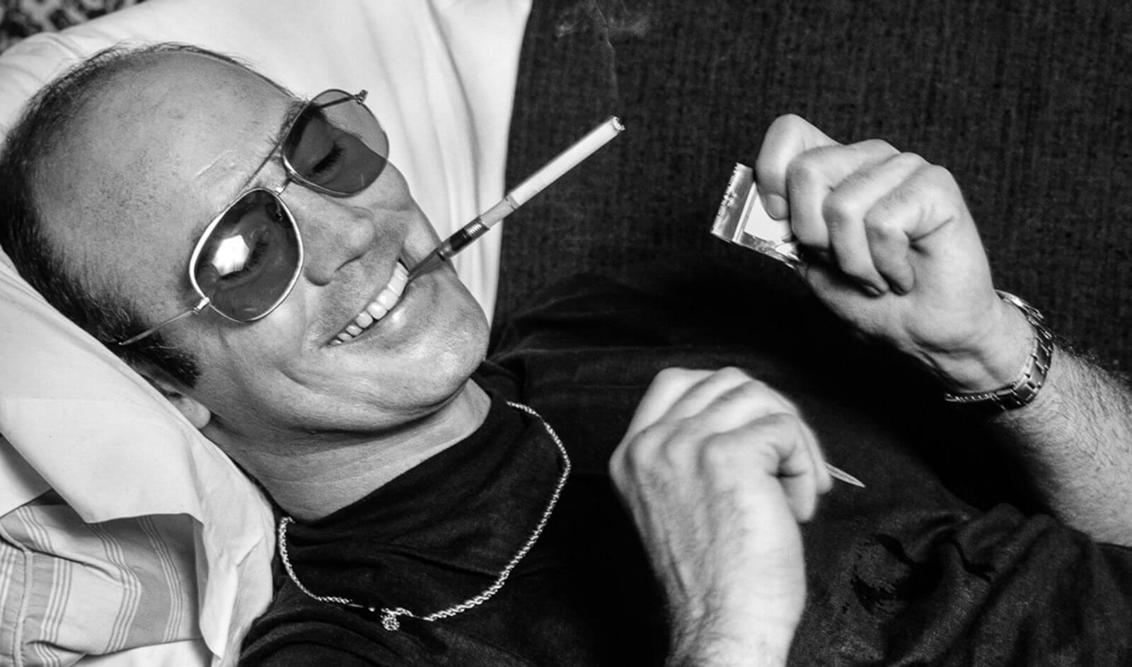 Pisarz Hunter S. Thompson leżący w okularach przeciwsłonecznych z papierosem