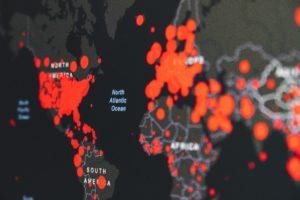 Czarna mapa polityczna z zaznaczonymi na czerwono ogniskami zarażenia koronawirusem