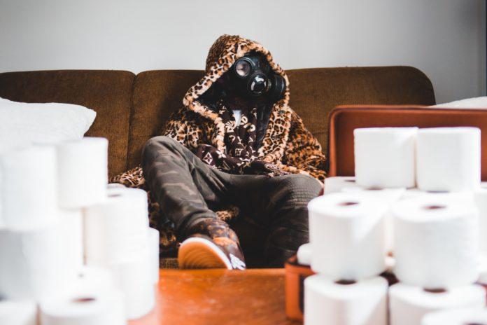 Mężczyzna w masce gazowej siedzi na kanapie ubrany w płaszcz w panterkę. Przed nim na stoliku dwie wieże z papieru toaletowego