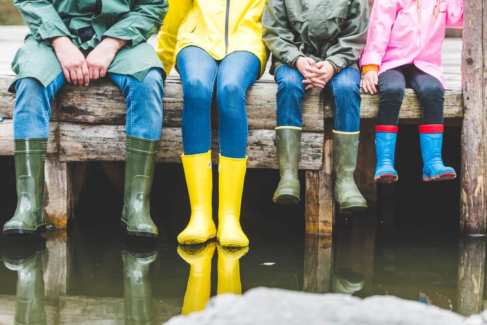 Rodzina siedzi na ławce w kolorowych gumowcach