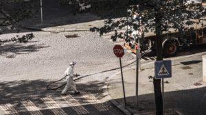 Człowiek ubrany w biały kombinezon ochronny dezynfekuje ulicę z gumowego węża