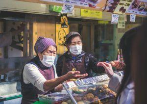 Dwie kobiety, stojące za ladą, noszące maseczki ochronne przyjmują płatność za produkty