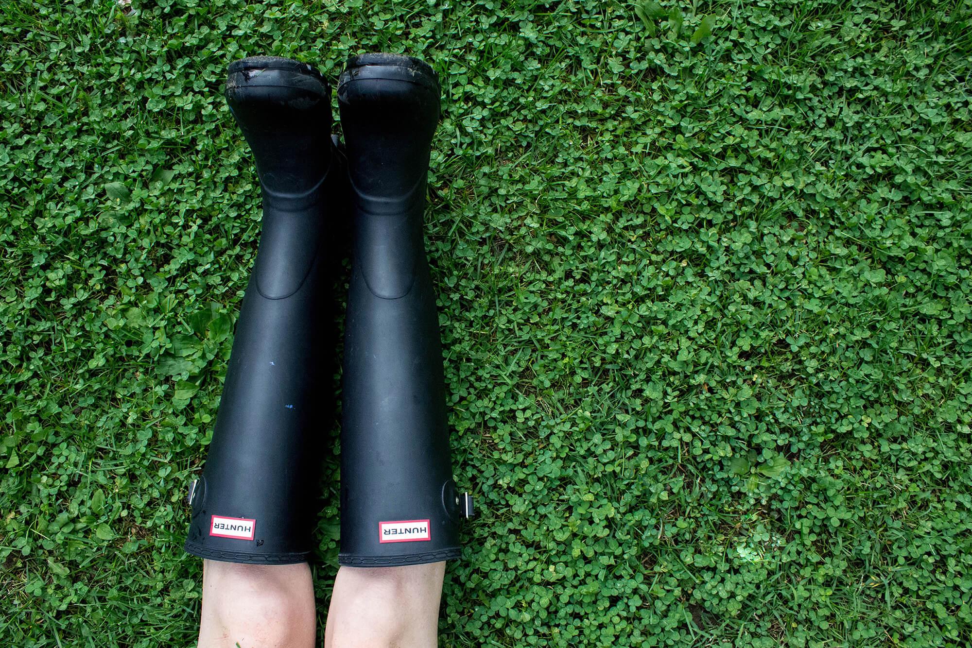 Nogi w czarnych gumowcach Hunters na trawie