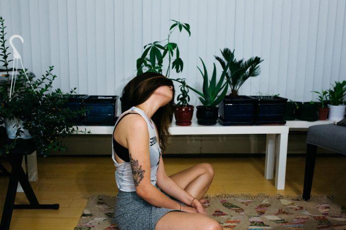 Dziewczyna z tatuażami ćwiczy na dywanie