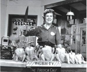 Zdjęcie telewizora z programem Julii Child w ręku trzyma nóż, przed nią ułożony rząd kurczaków