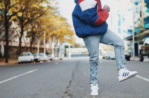 Moda uliczna chłopak w jeansach i sneakersach