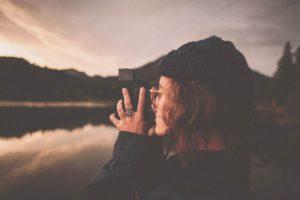 style w modzie Dziewczyna w czapce i okularach wykonuje analogowe zdjęcie