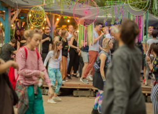 Zdjęcie z imprezy Fort BEfore. Kolorowo ubrani ludzie tańczący na otwartej przestrzeni