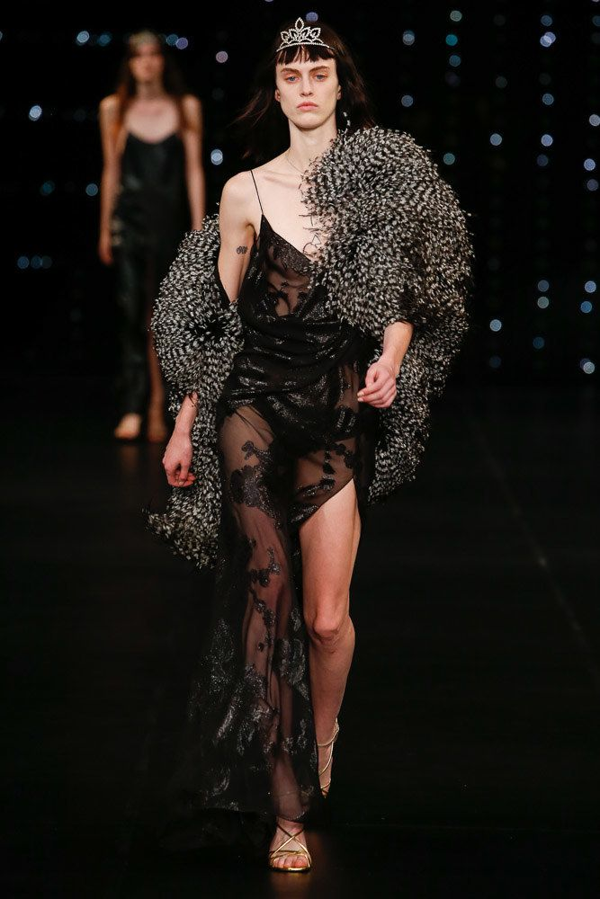 Modelka w czarnej slip dress idzie po wybiegu