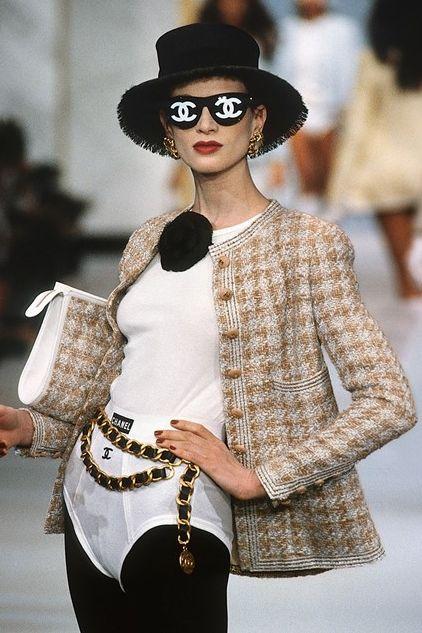 Modelka na wybiegu ubrana w tweedowa marynarka kapelusz i okulary