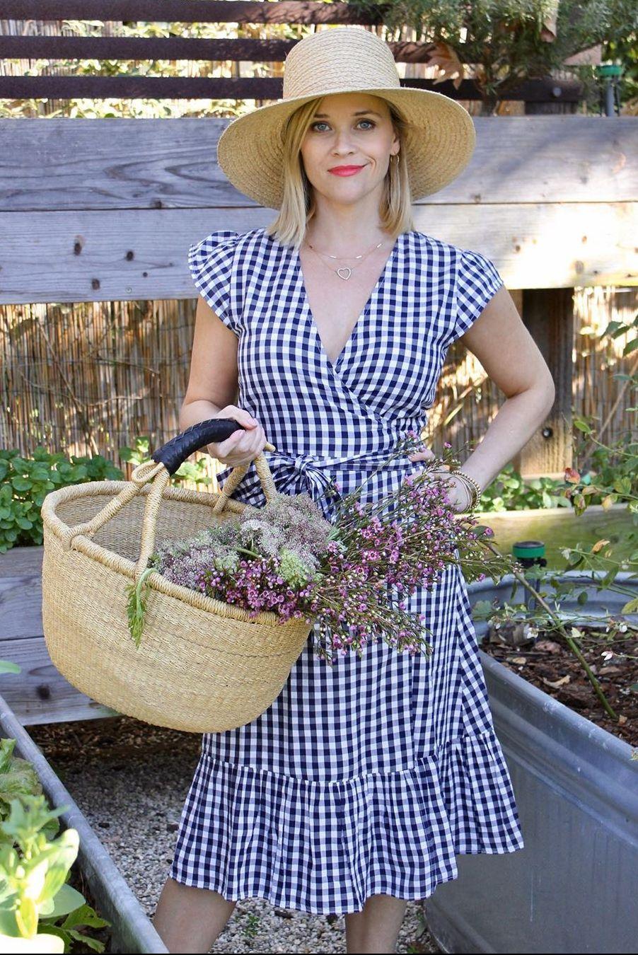 Blondynka ubrana w sukienki w krate ze słomianym kapeluszem na głowie i koszem pełnym kwiatów w rzece w szklarni