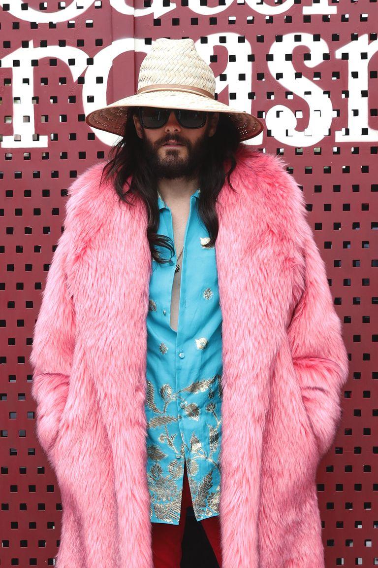 Mężczyzna w różowym futrze na ściance na głowie ma słomiany kapelusz
