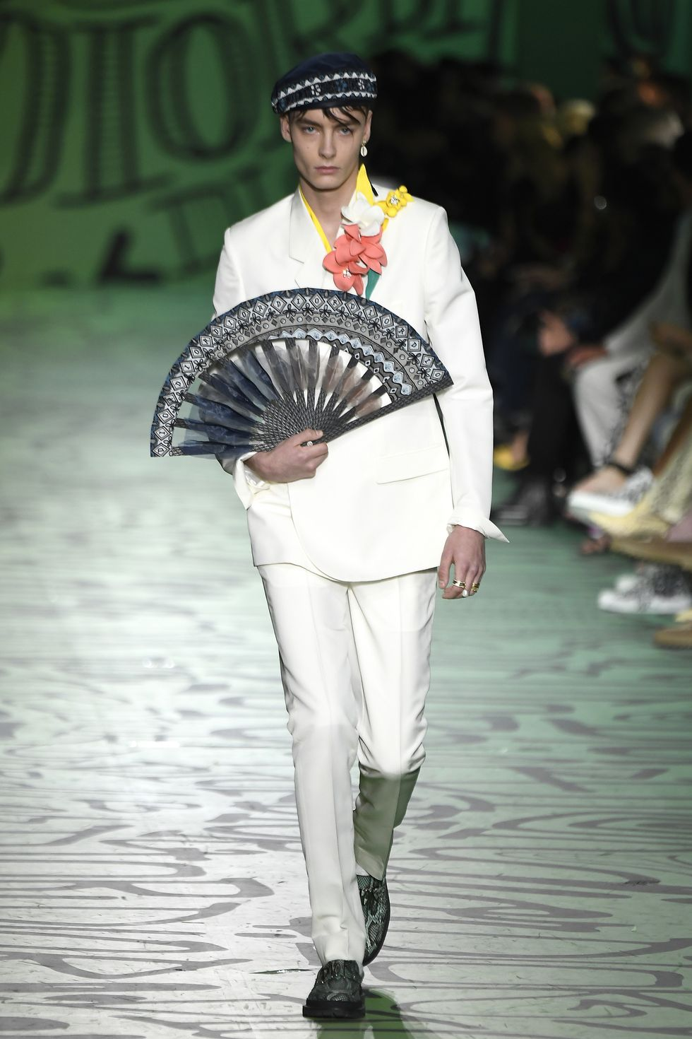 Model na wybiegu w białym garniturze z wielkim wachlarzem w dłoni