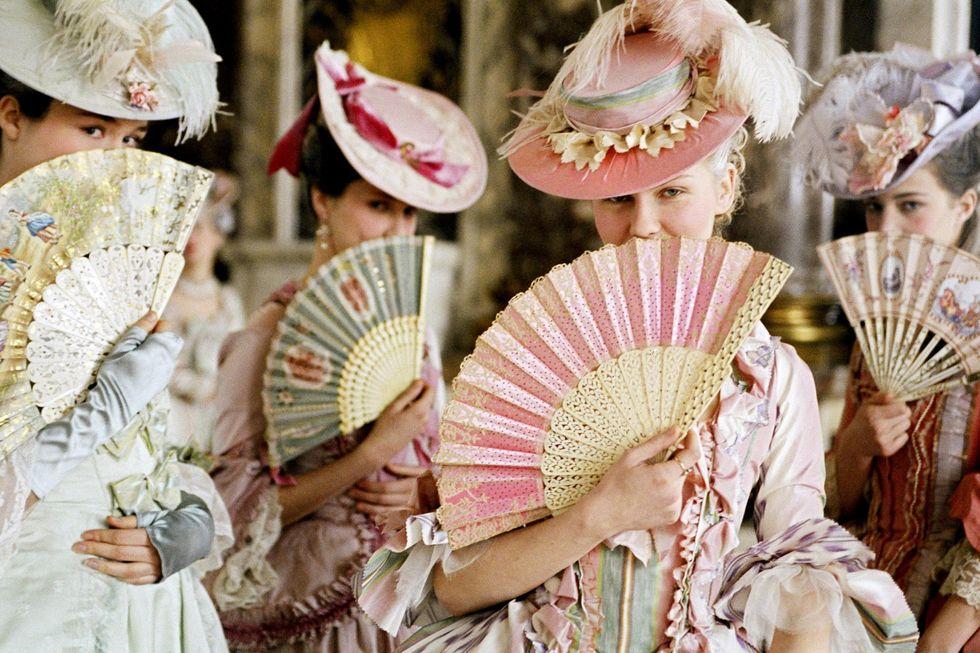 Cztery kobiety ubrane w suknie z dawnych lat zasłaniają twarz wachlarzami