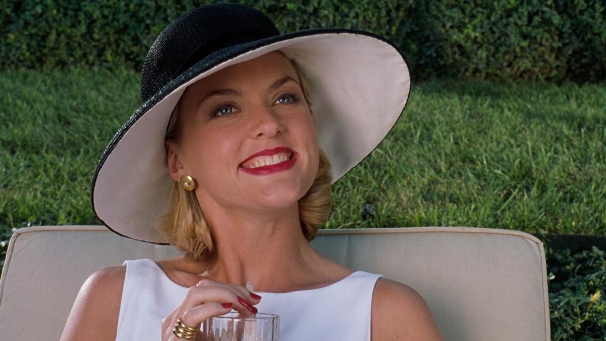 Portret kobiety w dużych slomianym kapeluszu sączącej drinka