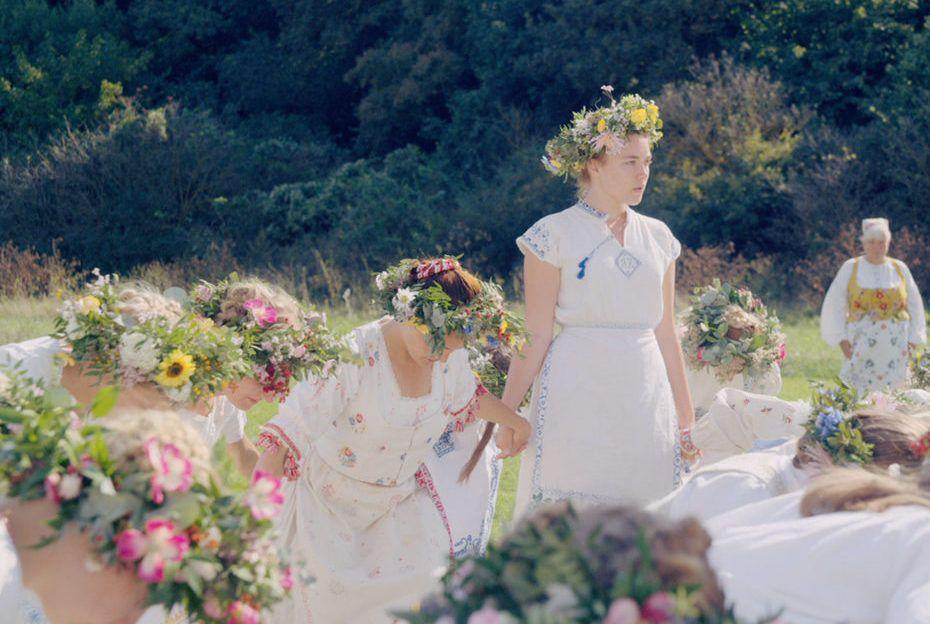 kobiety ubrane w białe koszule i wianki stoją w kręgu