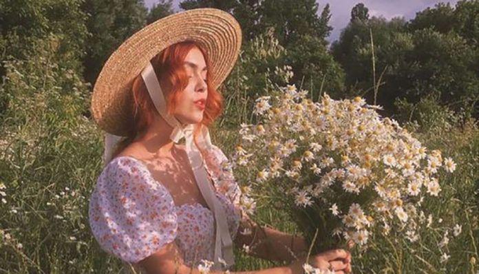 Dziewczyna w kapeluszu na lace z kwiatami