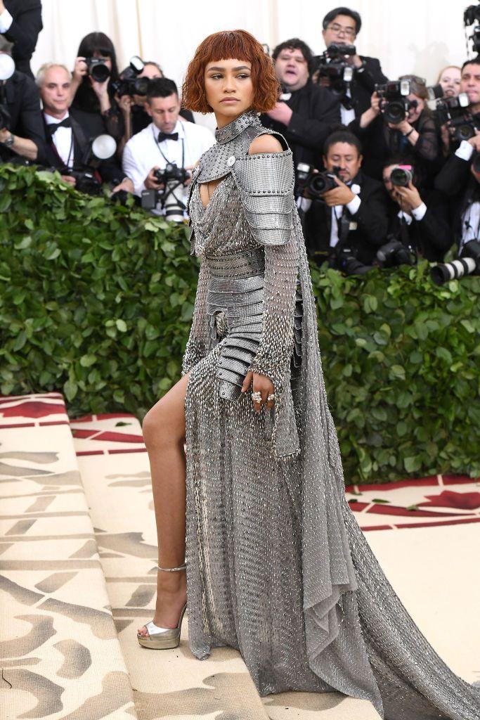 Aktorka w sukni przypominająca zbroje wspina cie po schodach