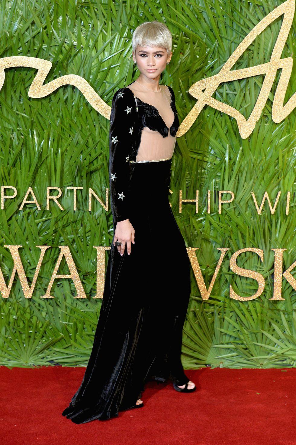 Aktorka na zielonej ściance i czerwonym dywanie ubrana w czarna suknie