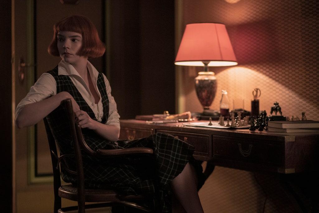 Młoda dziewczyna siedzi w półmroku przy stole zastawionym szachami