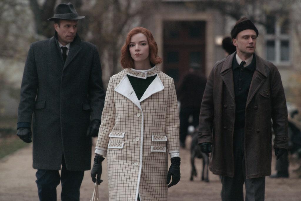 Młoda dziewczyna ubrana w kraciasty płaszcz przemierza ulice w towarzystwie dwóch rosłych mężczyzn