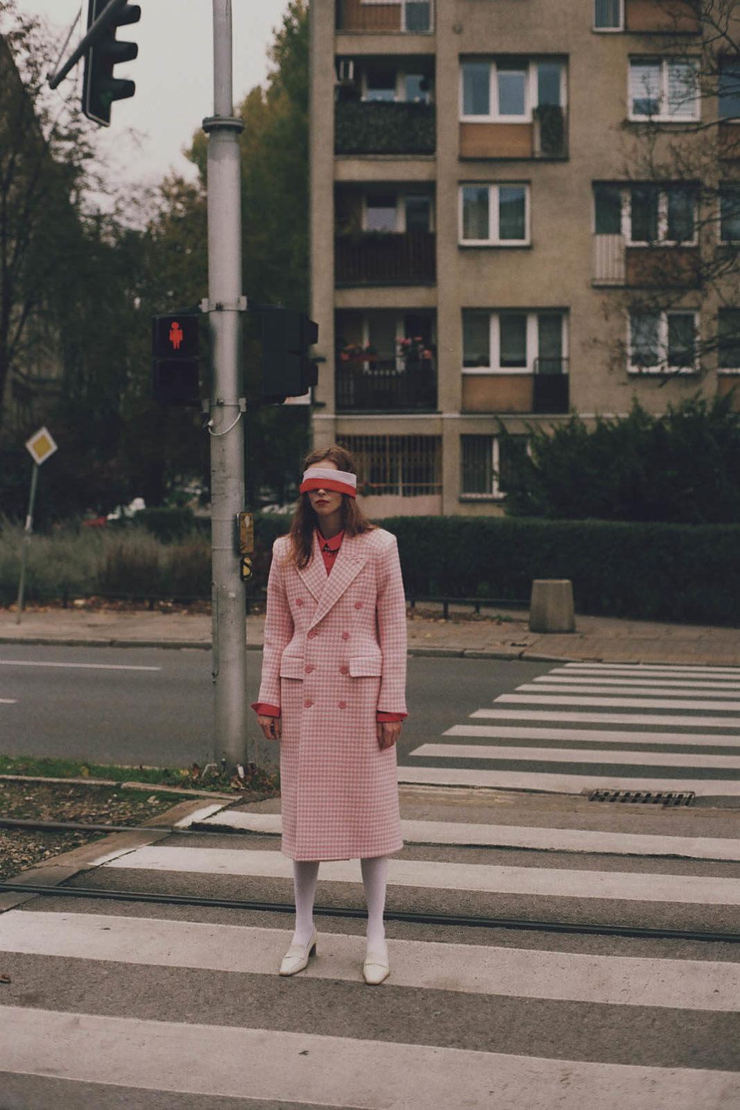 kobieta z biało czerwoną przepaską na oczach stoi na przejściu dla pieszych