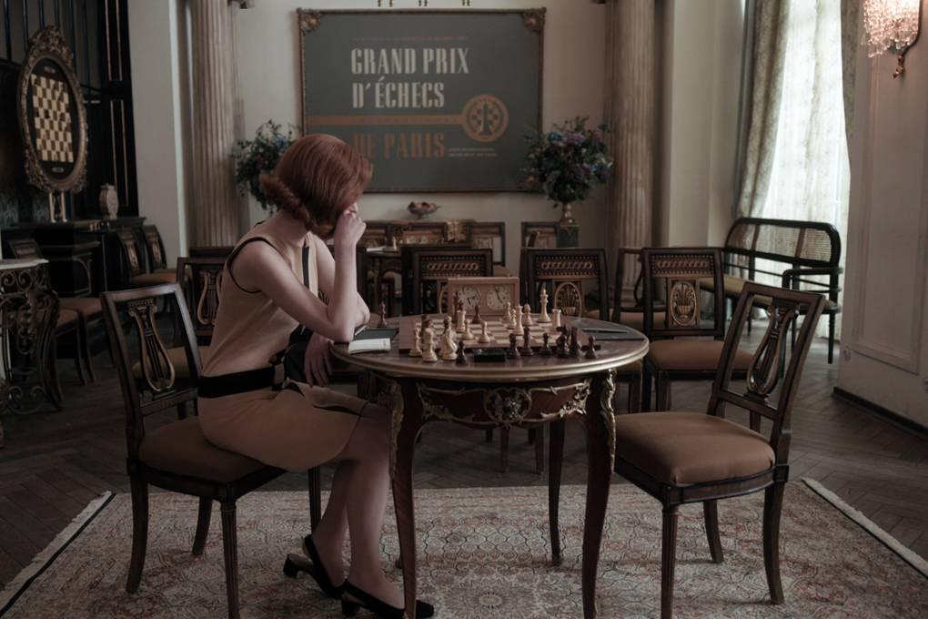 Młoda dziewczyna siedzi i patrzy na szachy, ktore sa na stoliku