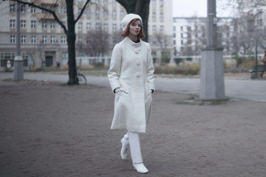 Młoda kobieta przemierza ulice w białym płaszczu białych butach i białym kapelusiku