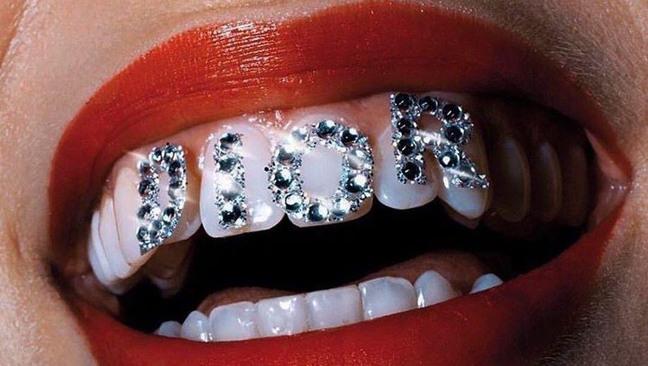 zdjęcie uśmiechniętych ust z napisem z diamentów dior na zębach