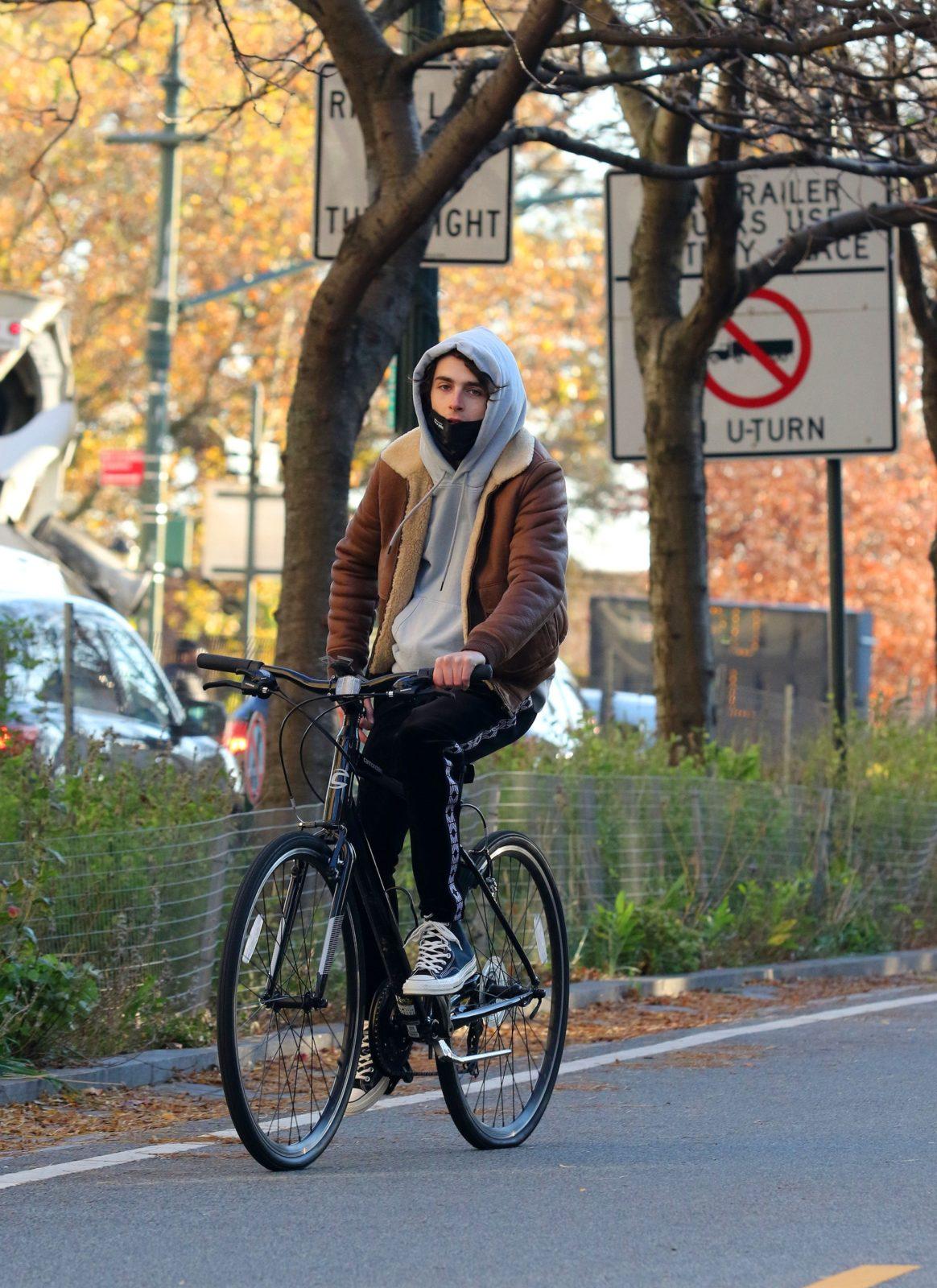 Mlody mężczyzna przemierza ulice na rowerze