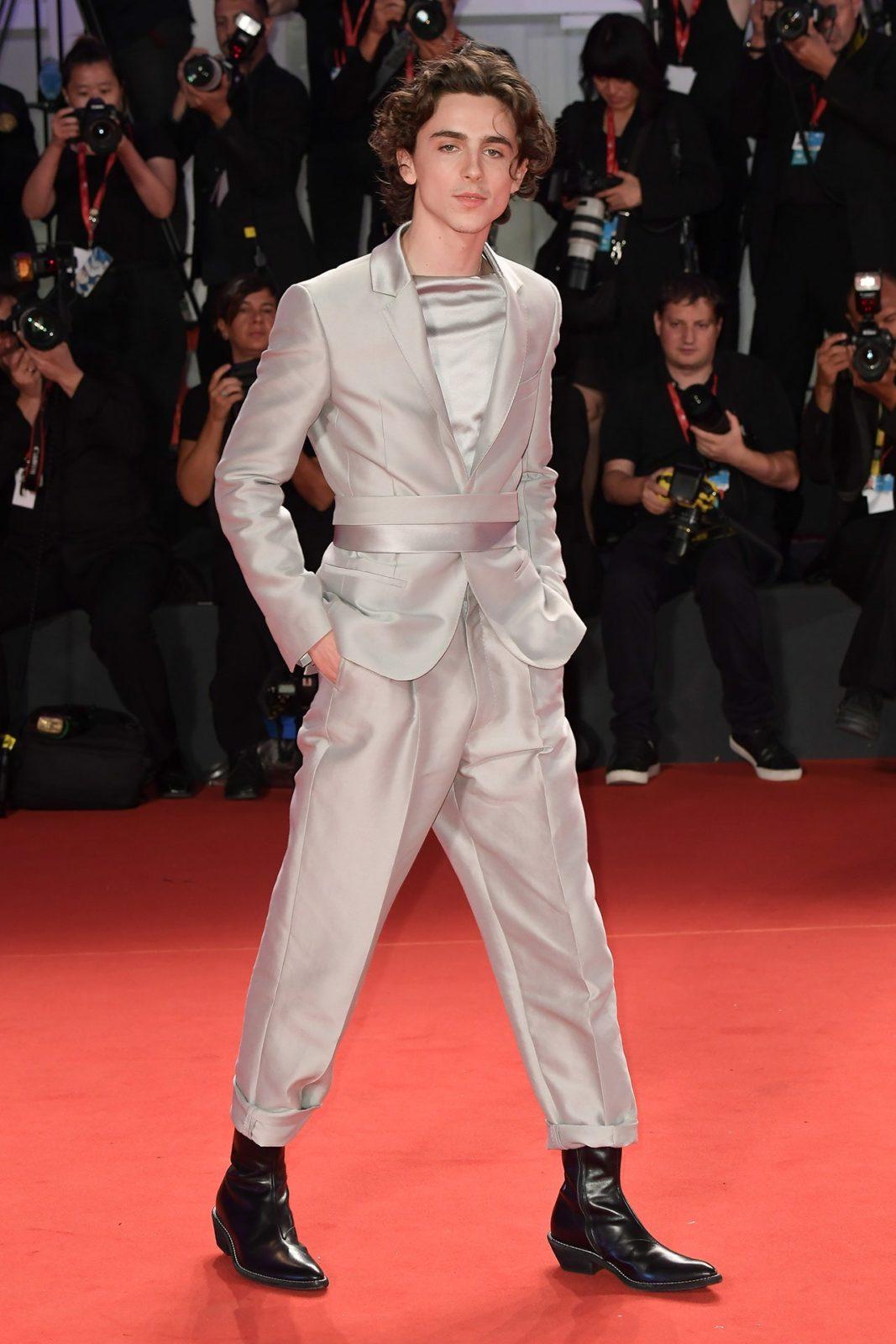 Młody aktor w srebrnym garniturze na czerwonym dywanie