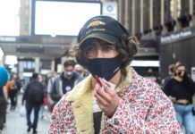 Mlody mężczyzna w masce i czapce z daszkiem na ulicy